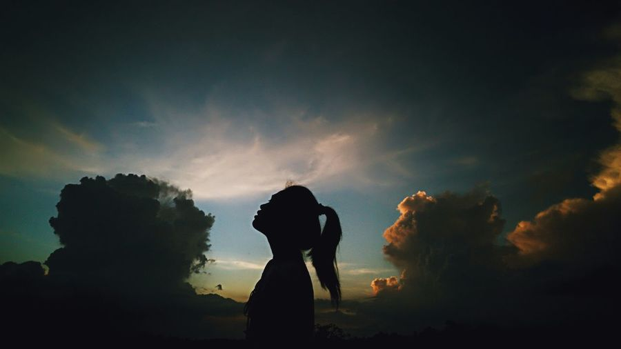 Side view of silhouette woman standing against sky during sunset