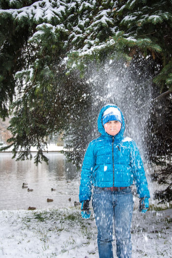Portrait of boy standing amidst falling snow at park