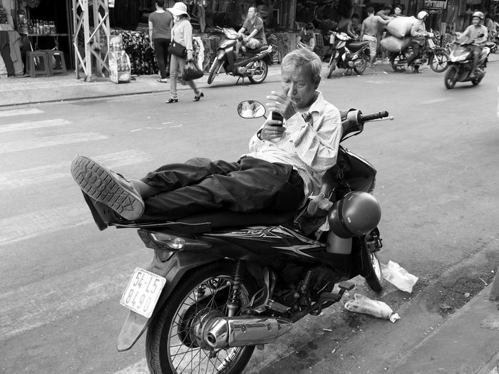 A scooter is also a place to rest, where you can consult your smartphone. In Ho-Chi-Minh City, Vietnam Full Length Mode Of Transportation Transportation Man Street City Real People Bnw_friday_eyeemchallenge Bnw_motorcycles