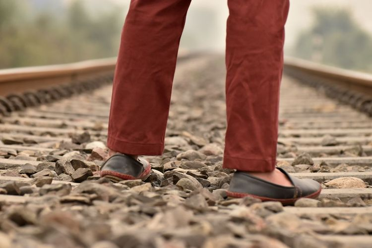 Low section of man standing on gravel at railroad track