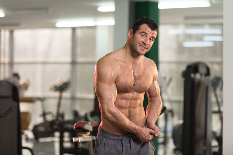 Portrait of smiling shirtless man exercising in gym