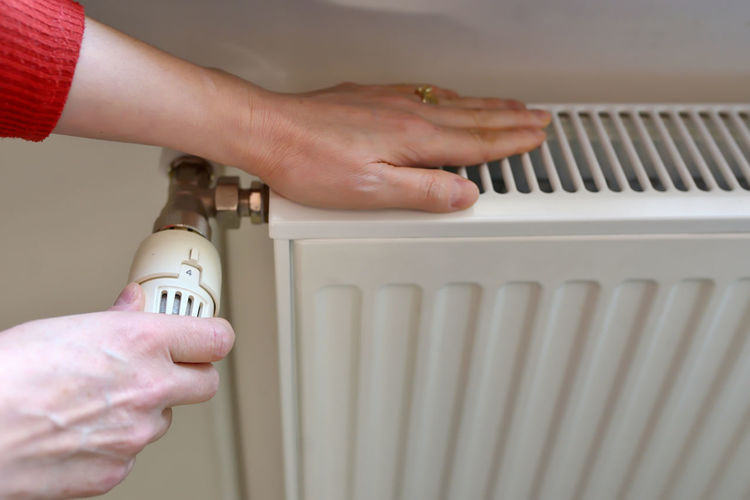 Cropped hands of woman repairing radiator at home