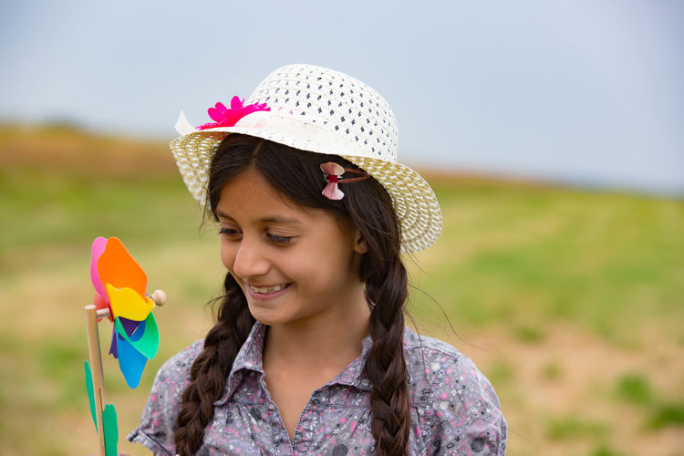Smiling girl holding pinwheel while standing on field