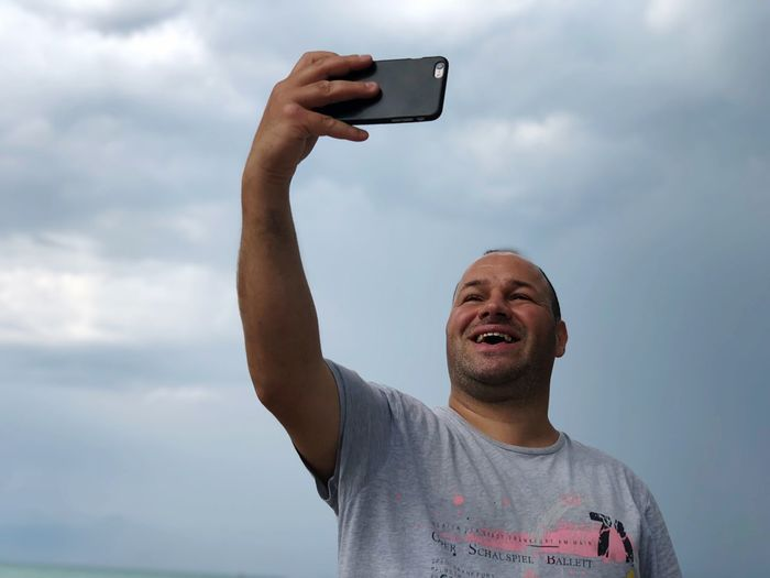 Man taking selfie while standing against cloudy sky