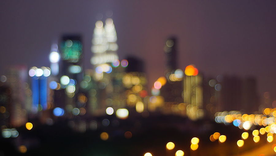 Malaysia city skyline illuminated at night.Blurry photo light and bokeh. Architecture Building Building Exterior Built Structure City City Life Cityscape Defocused Financial District  Glowing Illuminated Lens Flare Light Lighting Equipment Multi Colored Night No People Office Building Exterior Outdoors Skyscraper Street Transportation Travel Destinations Vehicle Light
