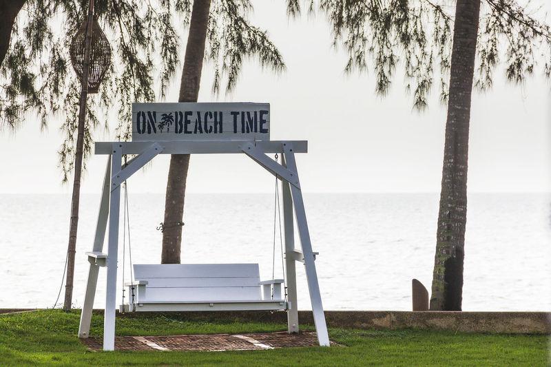 White wooden swings on the lawn at thap sakae beach prachuap khiri khan, thailand