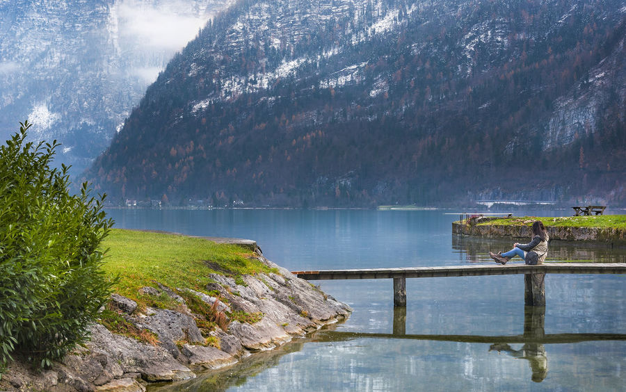 Young woman sitting on a wooden deck, relaxing and admiring the majestic Dachstein Mountains and the Hallstatter lake, located in Hallstatt, Austria. Austrian Alps Austrian Lakes Mountain View Water Reflections Beauty In Nature Day Early Winter Hallstatt Hallstatt, Austria Hallstattersee Lake Lake Reflection Mountain Nature Outdoors Scenics Sky Tranquility Water