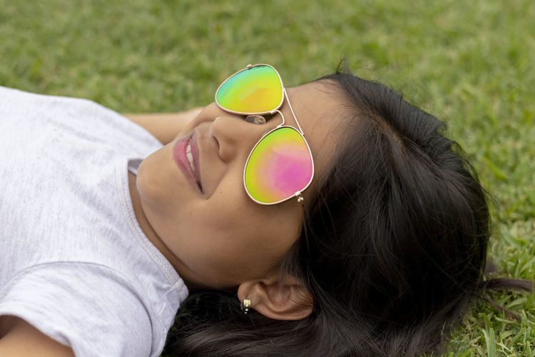 Beautiful girl with sunglasses lying on the grass Glasses Sunglasses One Person Headshot Leisure Activity Fashion Portrait Lying Down Lifestyles Young Adult Real People Women Young Women Long Hair Hair Relaxation Hairstyle High Angle View Day Lying On Back Outdoors Beautiful Woman
