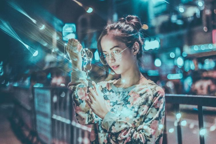 Portrait of young woman holding illuminated city at night