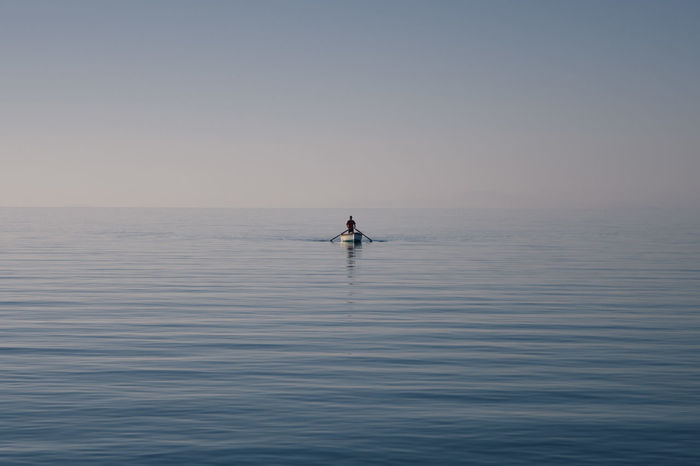 Man on boat sailing in sea against clear sky