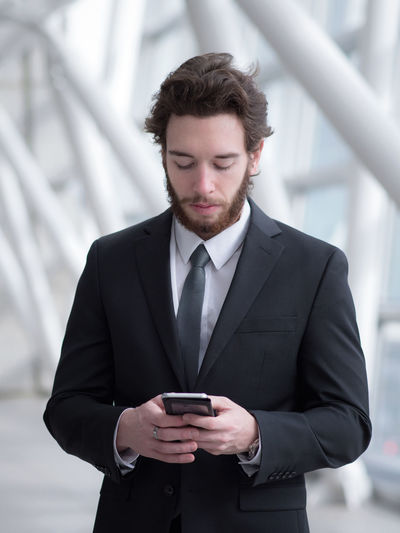 Businessman Using Mobile Phone While Standing In Building