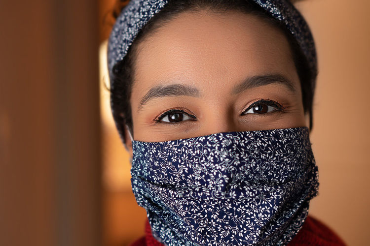 Portrait of smiling woman wearing mask standing at home