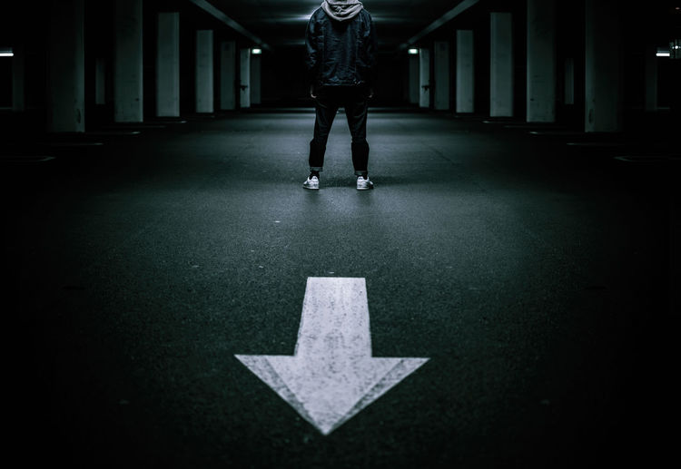 Low section of man standing by arrow symbol on road at underground parking lot
