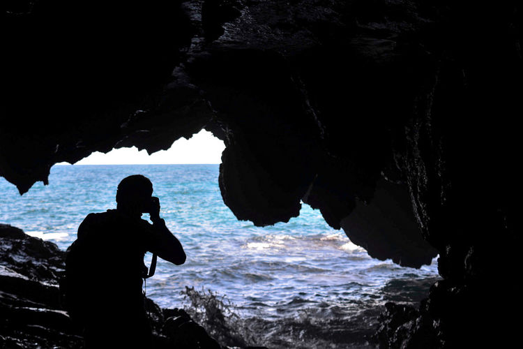 Silhouette man standing in cave against sea