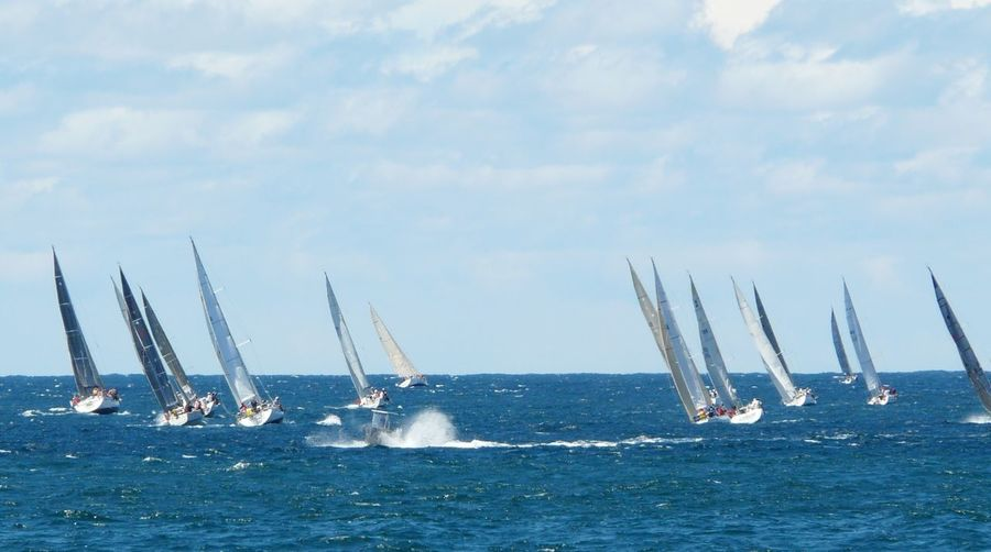 Yatch race at sea against sky