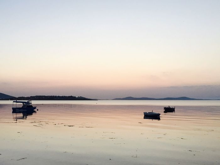 Silhouette boats in sea against clear sky at sirinkent sahil