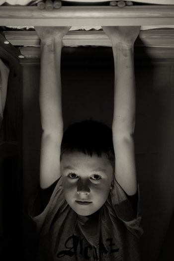 Portrait of playful boy holding roof beam