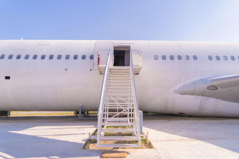 Abandoned airplane at airport against sky