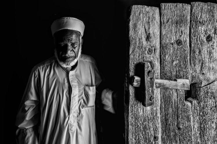Portrait of man standing against door