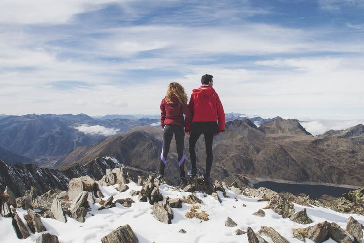 Rear view of couple standing on snowcapped mountains against sky