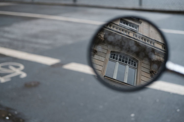 High angle view of building reflecting on side-view mirror against road