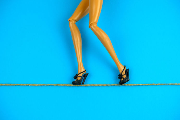 Low section of figurine walking in high heels on rope against blue background