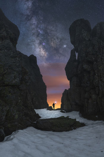 Scenic view of rock formations in sea against sky at night
