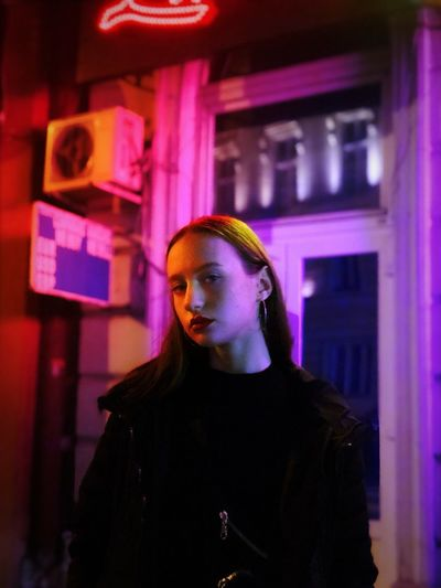 Portrait of young woman standing in illuminate city