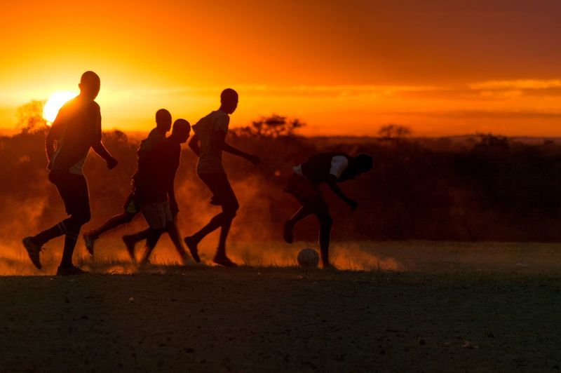 People playing soccer on field during sunset