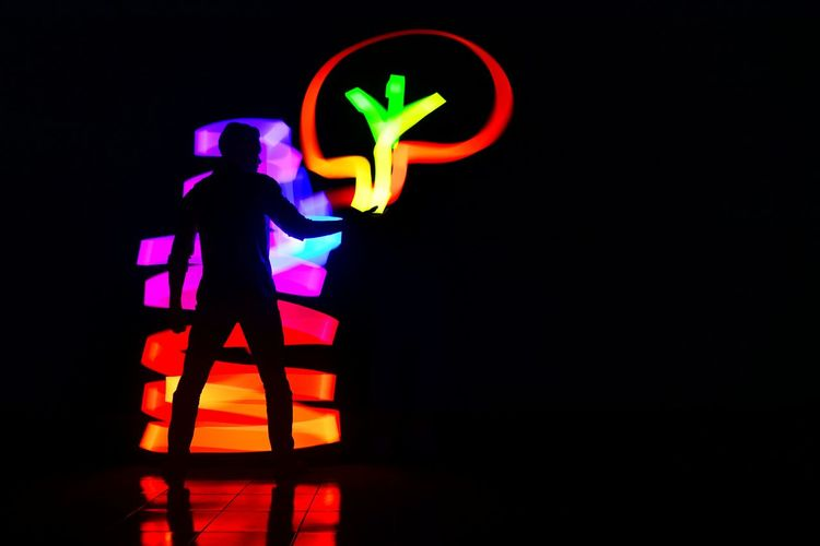 Silhouette person standing against illuminated light painting