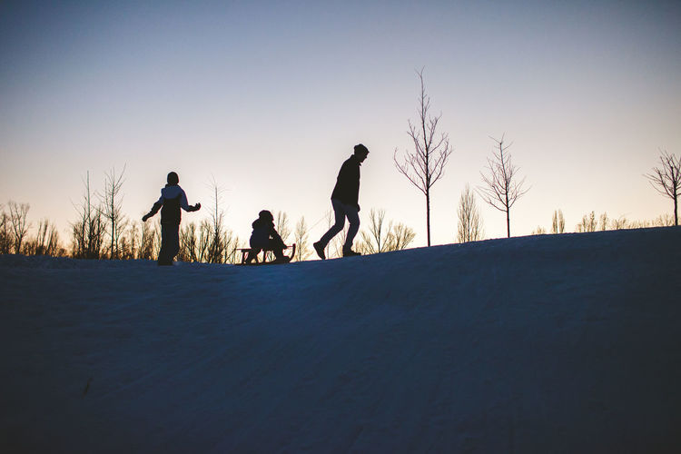 Silhouette people on snow covered land against sky during sunset
