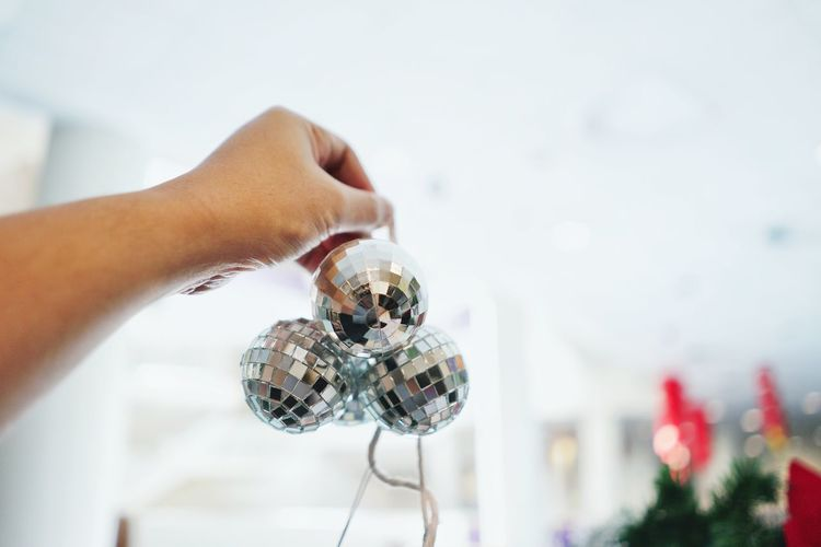 Cropped Hand Holding Baubles At Home