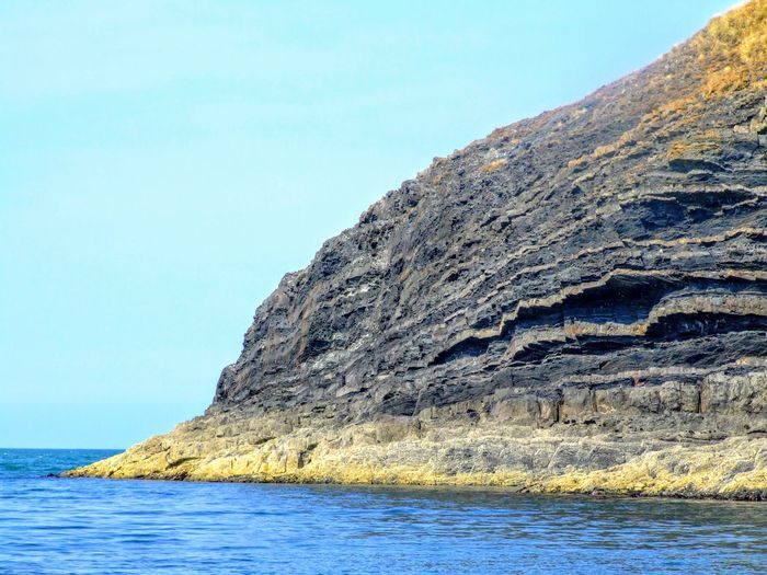 Rock formations by sea against clear blue sky