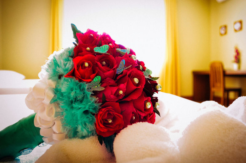 Close up of red rose bouquet on bed at home