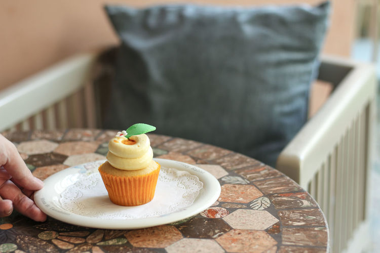 Close-Up Of Hand Holding Cupcake In Plate By Chair