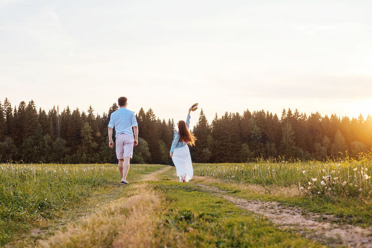 Rear view of couple walking on grass against sky