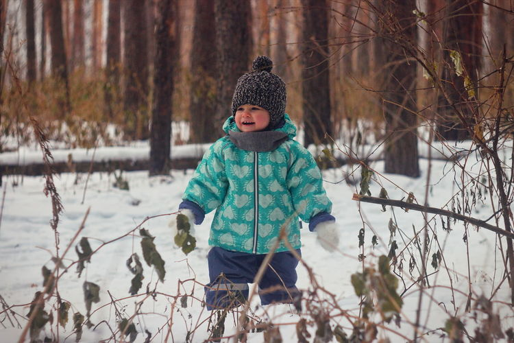 Cheerful baby girl standing in forest during winter