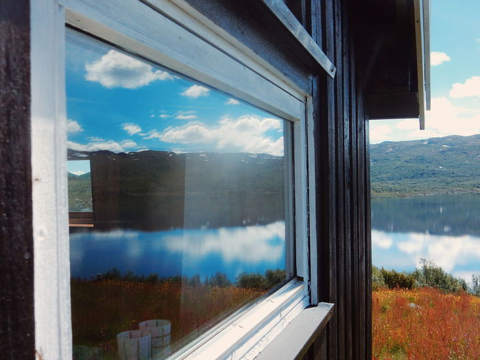 Reflection of mountain and lake on house window