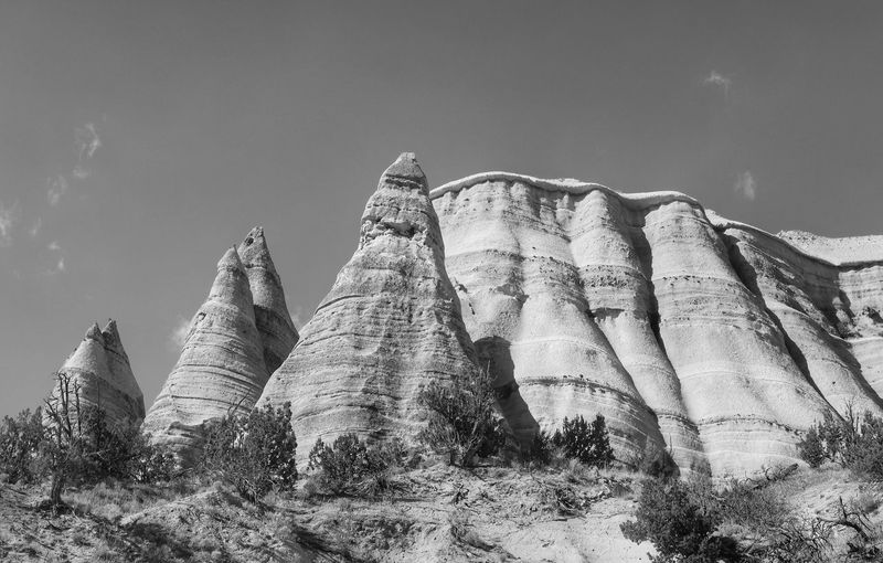 Black and white low angle landscape of tent like rock formations in Kasha Katuwe Tent Rocks National Monument New Mexico Triangular Kasha-Katuwe Tent Rocks National Monument Kasha-Katuwe Black And White Low Angle View Sky Nature History No People The Past Plant Day Travel Destinations Tranquility Outdoors Solid Sunlight Travel Rock Rock Formation