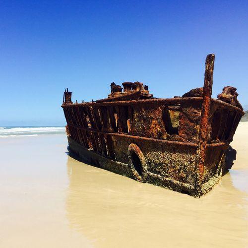 Ship wreck at beach against clear blue sky