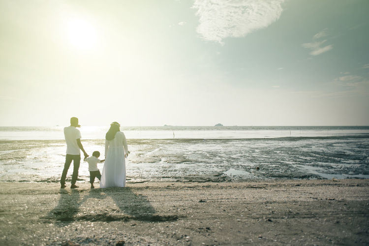 Happy family standing on shore at beach against sky