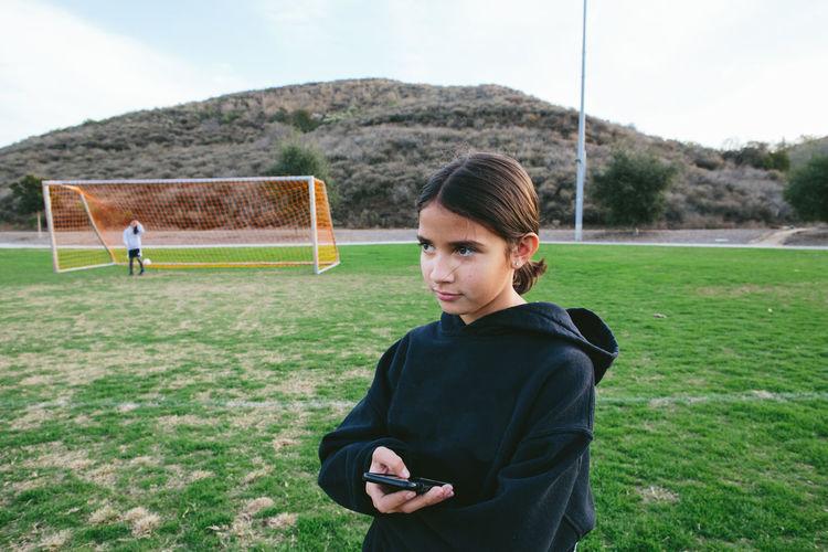 Portrait of teenage girl holding ball on field