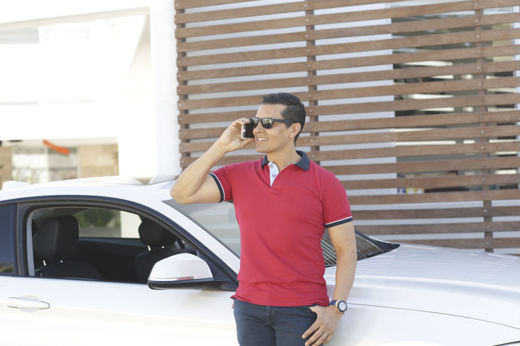 Smiling man talking on smart phone while standing by car in city