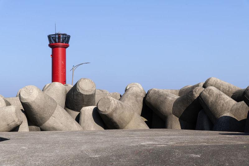 Lighthouse against rocks against clear blue sky