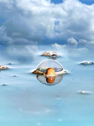 Digital Composite Image Of Egg Splashing On Water Against Sky