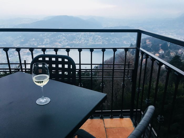 Close-up of wineglass on table by railing against landscape