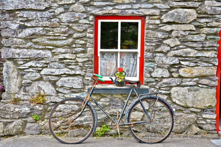 It was a great bike in its day. Mission Kenmare, County Kerry, Ireland Ireland Bicycle Wall - Building Feature Window No People Architecture Building Exterior Stone Building Stone House Red Flowers Flowers In A Teapot Old Bicycle Tourist Destination Stone Wall Outdoors Mode Of Transportation House Day Historic Historic Building Building Built Structure