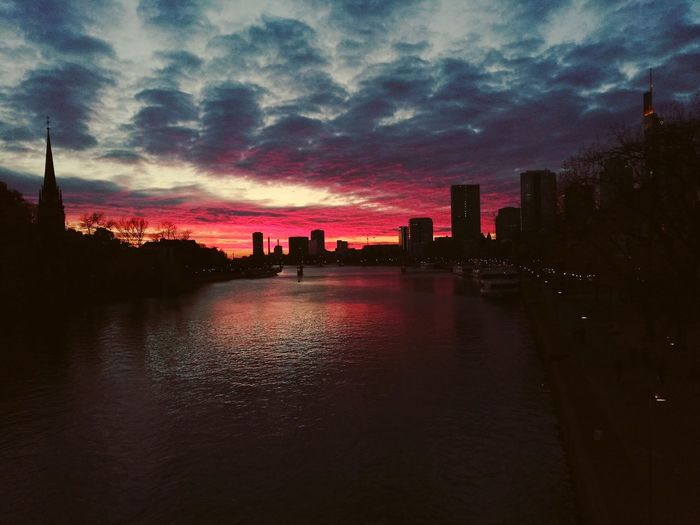 Silhouette buildings by river against sky during sunset