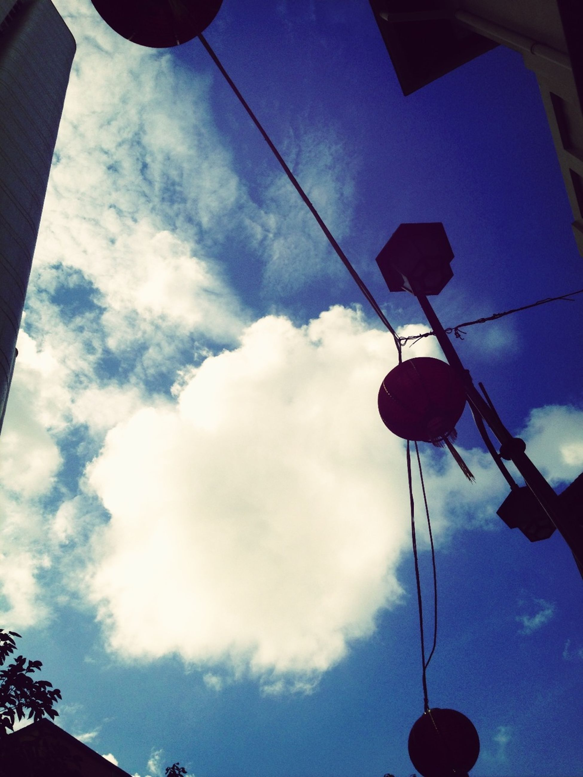 low angle view, lighting equipment, sky, street light, electricity, hanging, built structure, cable, architecture, power line, cloud - sky, electric light, building exterior, lantern, illuminated, cloud, silhouette, blue, no people, outdoors