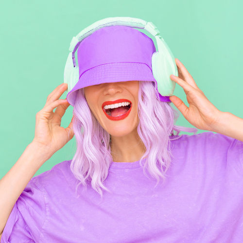 Side view of woman wearing hat and headphones against colored background